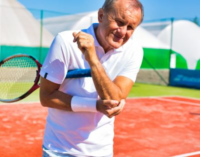 Senior man with elbow pain standing with tennis racket