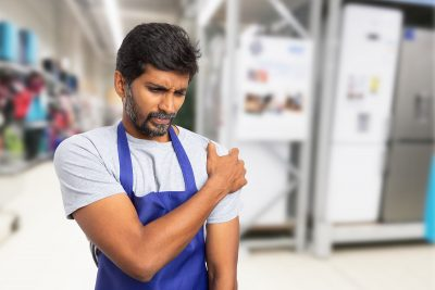 Indian Man Working At Supermarket Holding Painful