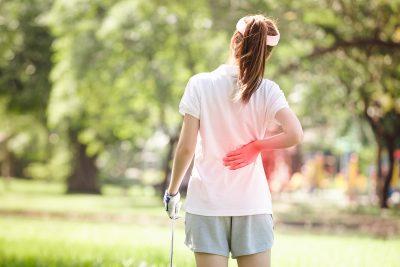 Female golfer holding her back in pain