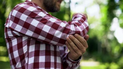 Man in checkered shirt holding elbow in pain
