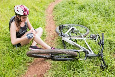 Woman holds knee in pain sitting next to crashed bike