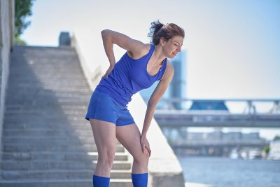 Athletic woman in blue workout clothes rubbing her painful lower back