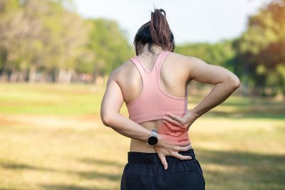 Athletic woman in running clothes rubbing her painful lower back