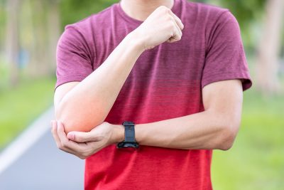 Athletic man in red shirt experiencing elbow pain during exercise