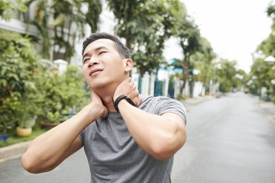 Athletic man massaging his painful neck