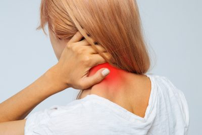 Blonde female holding her neck in pain