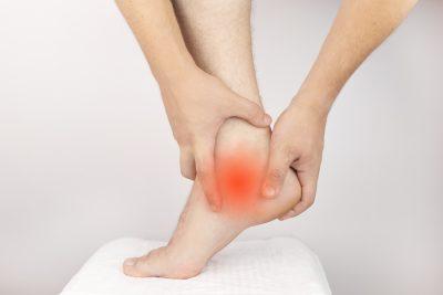 Man rubbing heel in pain